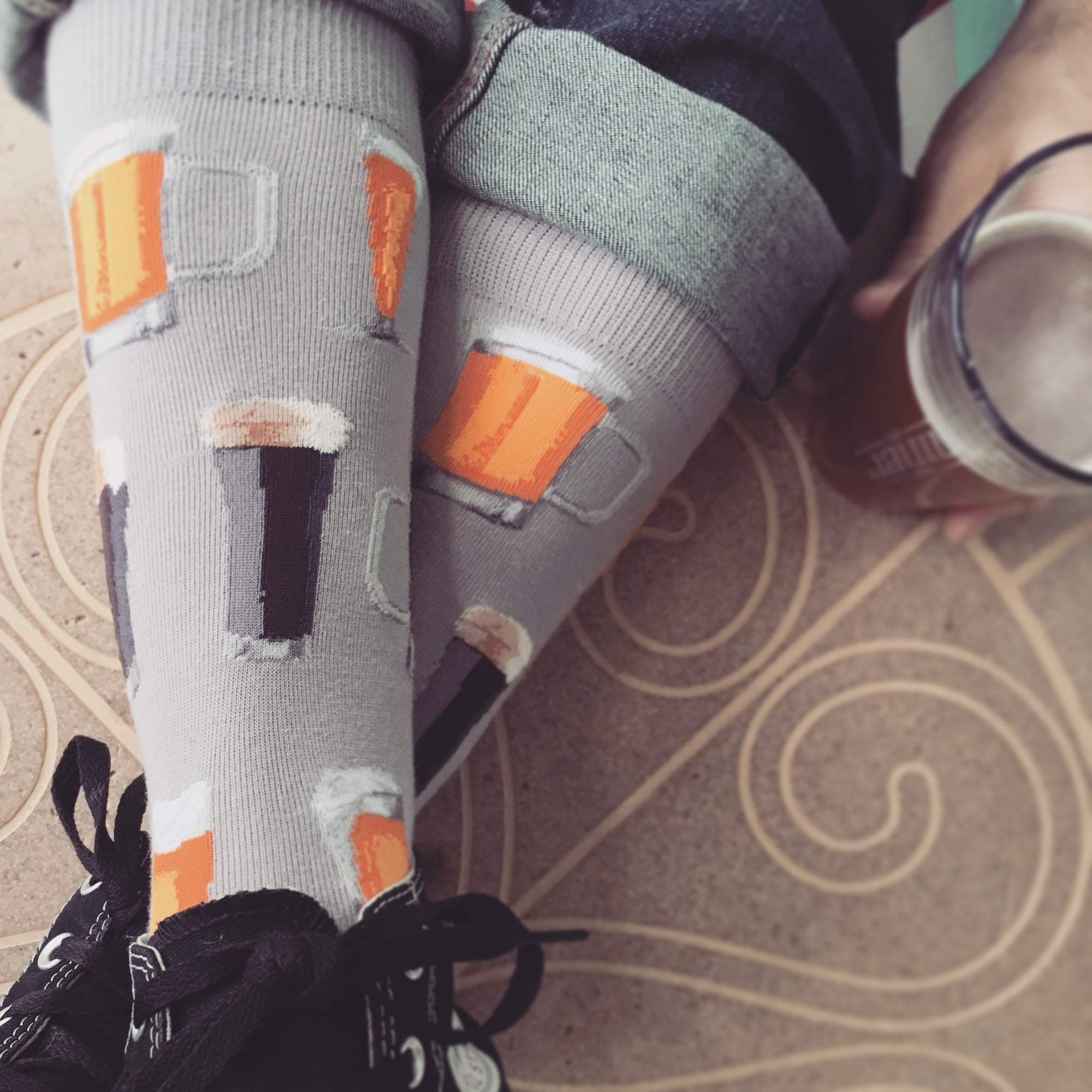 Beer socks featuring all sorts of brew on a gray background are worn by a beer enthusiast as he kicks back and drinks an IPA.