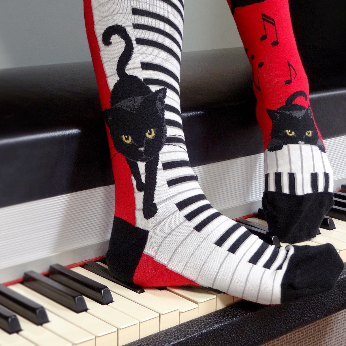 A black cat walks down piano keys while other cats play with music notes on these red knee socks for the music lover designed by sock brand ModSocks.