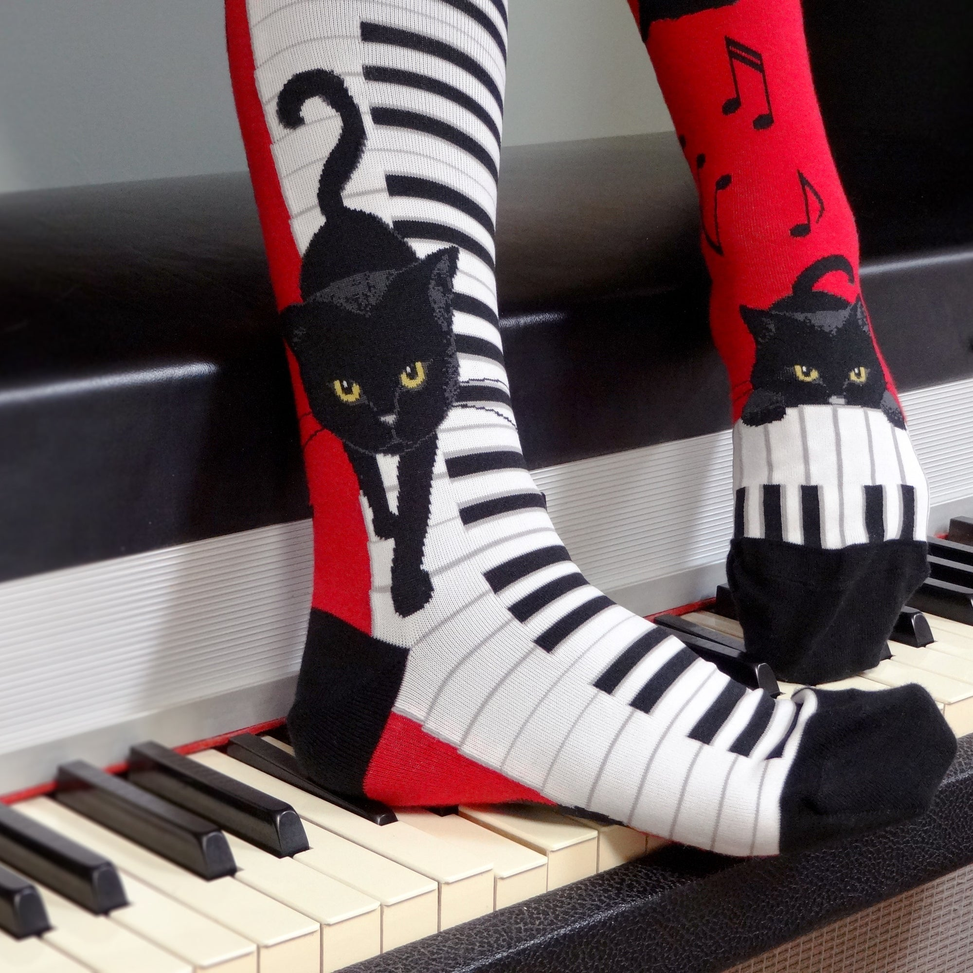 On these red knee highs with a black heel and toe are cute black cats with orange eyes prancing and playing on white and black piano keys with black music notes floating around them. In our Cat Socks collection you can find tons of cute cat socks!