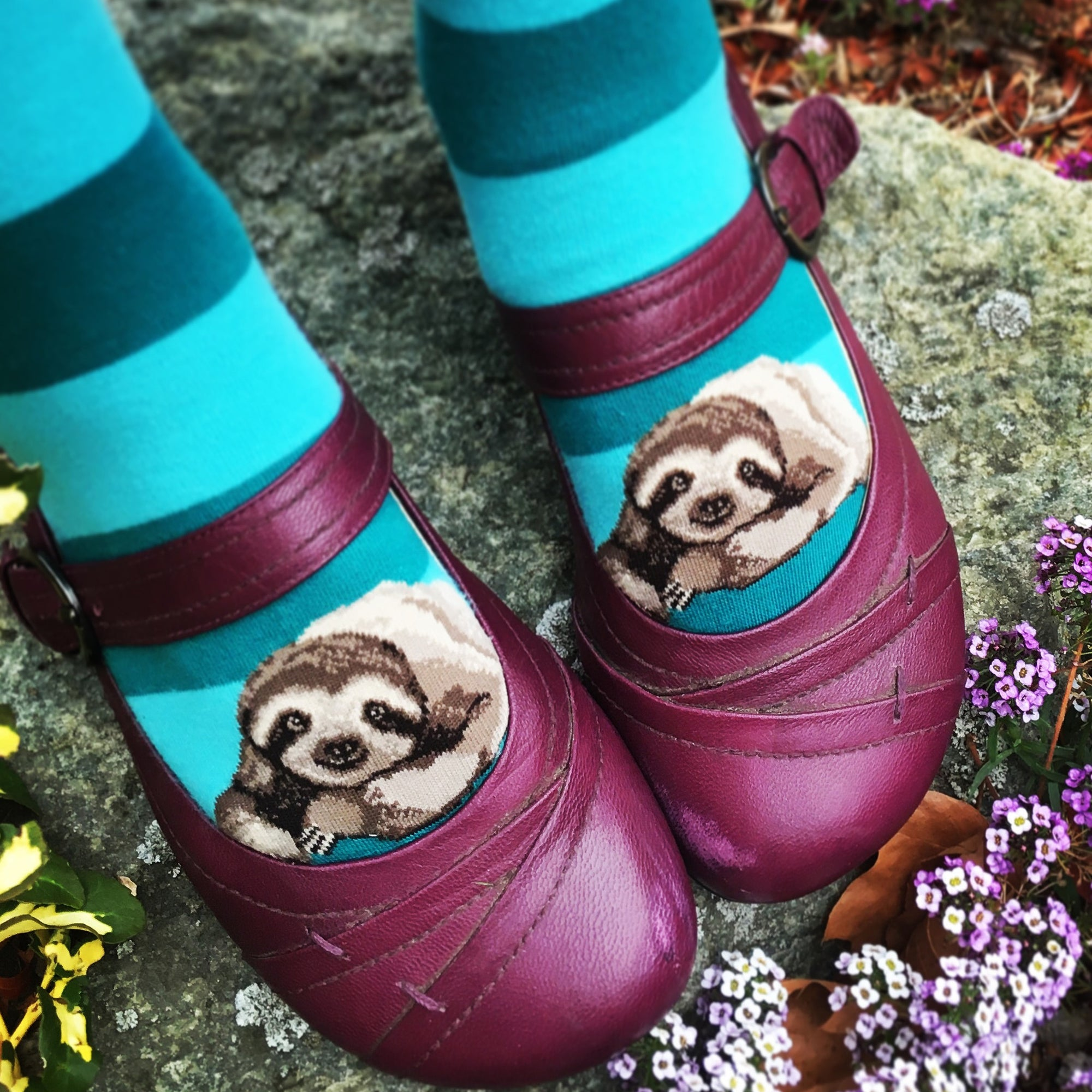 These cute teal striped sloth socks make it look like the sloths are peeking out from her purple Mary Jane shoes.