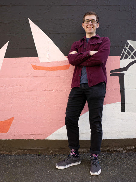 Benjamin Peterson of Cute But Crazy sock shop wearing cherry blossom floral socks standing in front of a sailboat mural in downtown Bellingham, WA.