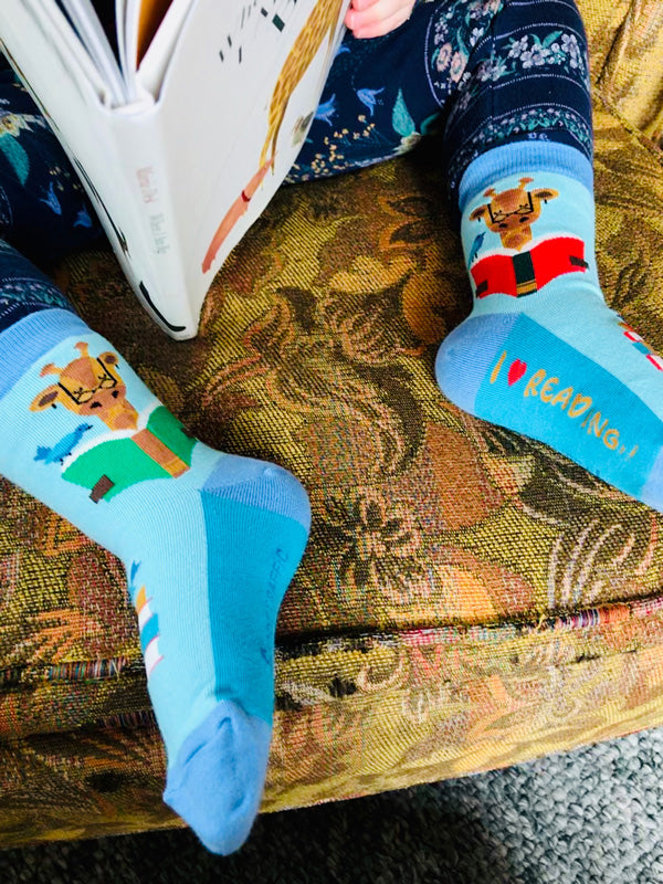 A child reads a  book while wearing kids' socks with books and giraffes