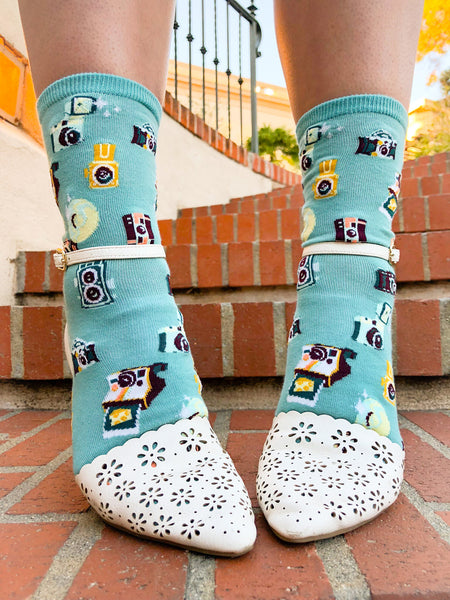Photography socks for women feature vintage and retro cameras including an instant camera printing a photo of a piece of cheese, all on a pale turquoise background.