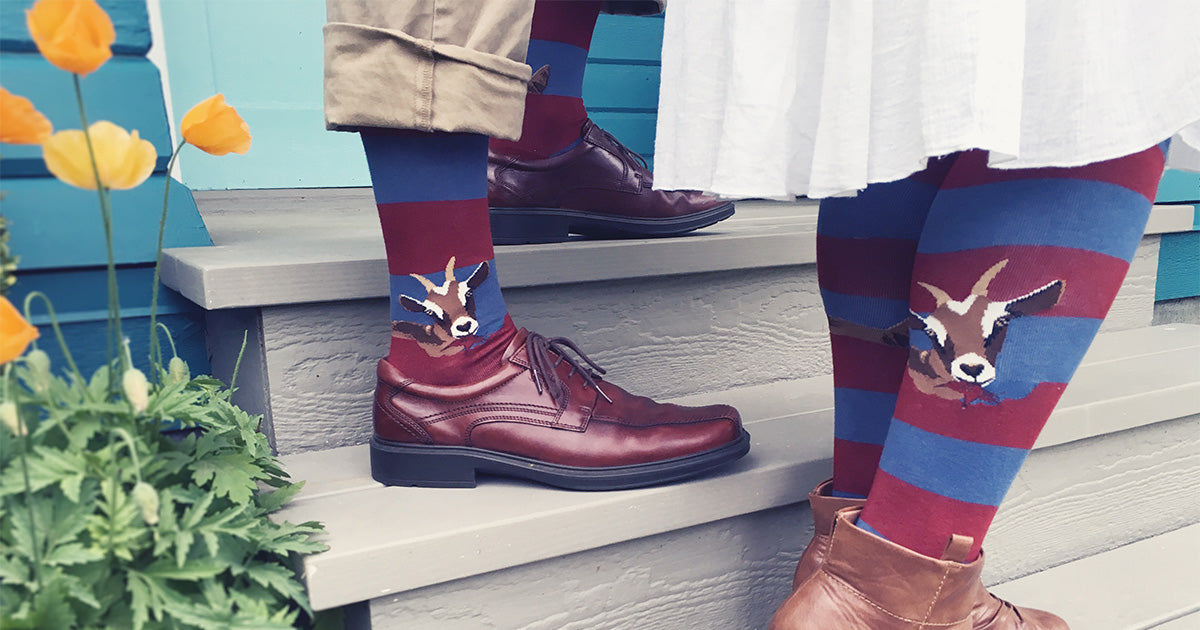 Goat socks on two people standing on a stoop with flowers beside them