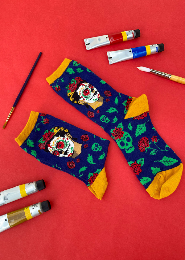 Day of the Dead Frida socks beside a set of paints