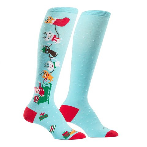 Women's holiday knee socks featuring cats leading Santa's sleigh