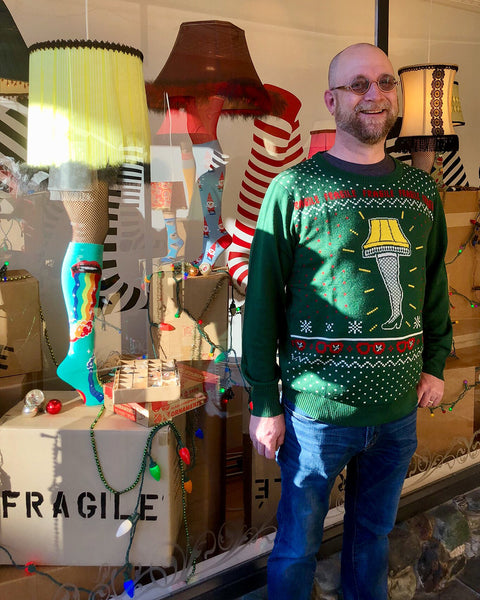 Man wearing a leg lamp ugly Christmas sweater in front of the shop's A Christmas Story window display.