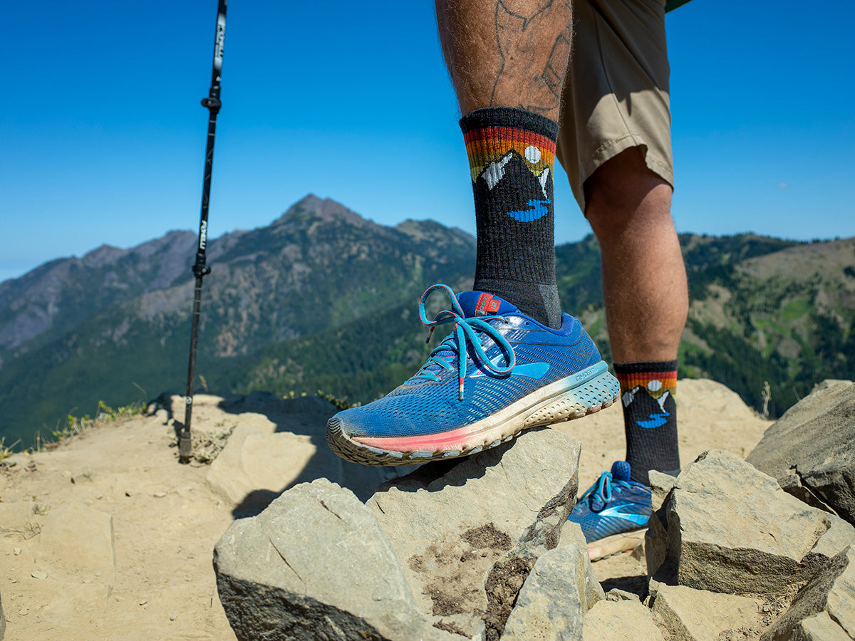 A hiker displays wool socks built for the trail with a mountain design