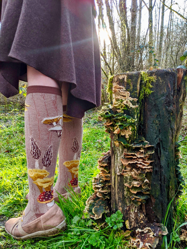 Mushroom Knee Socks stand beside a log covered in mushrooms in a sunny forest clearing