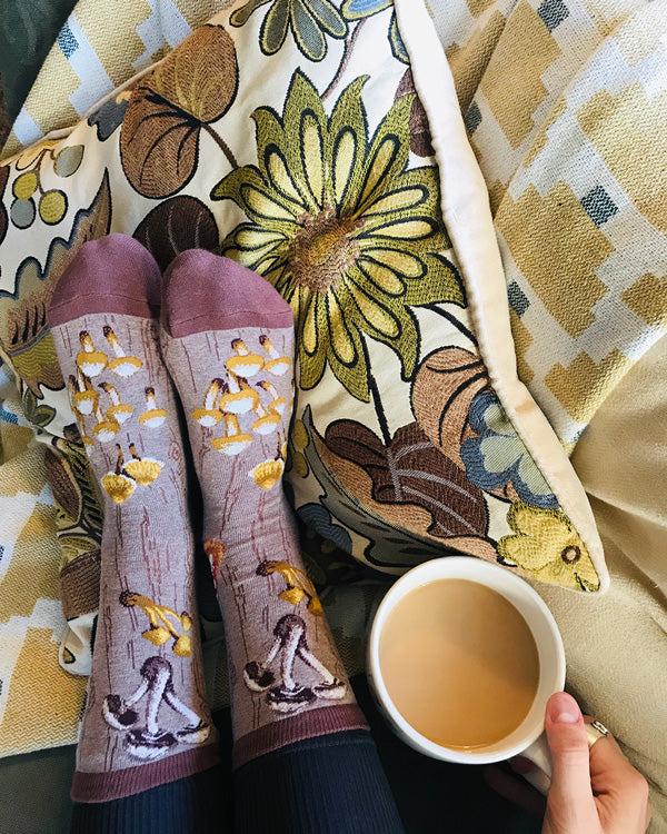 A person relaxes in cute mushroom socks with a mug of tea