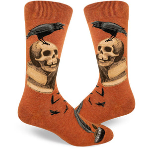 Edgar Allan Poe Socks for men with a raven on a skull on a stack of books.