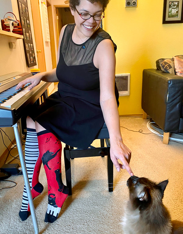 Lindsey wears Piano Cat Knee Socks with her cat Buddha
