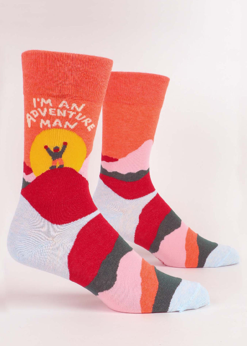 "Funny socks for men show a triumphant figure on top of a colorful mountain with the words, ""I'm an adventure man!"""