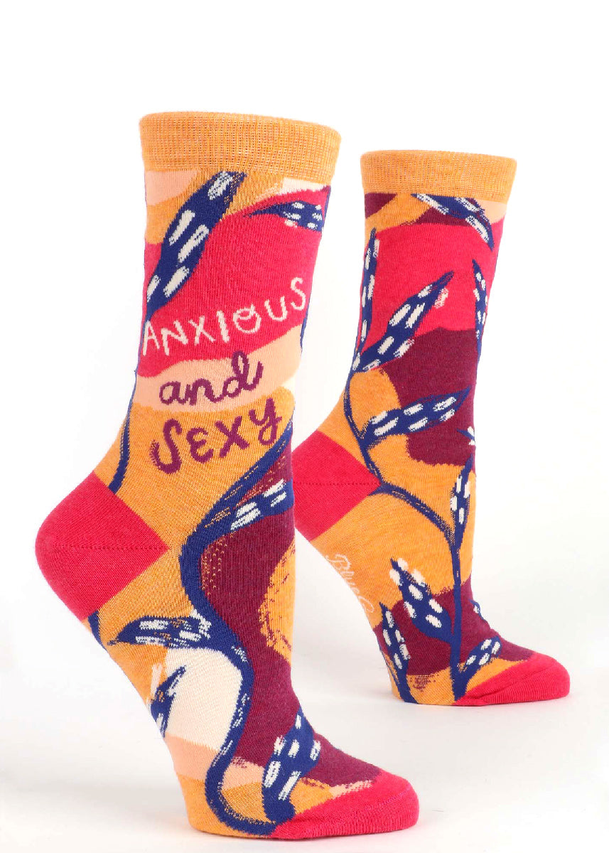 "Funny socks for women say ""Anxious and Sexy"" over a bold abstract background of red, orange, burgundy, and dark blue."