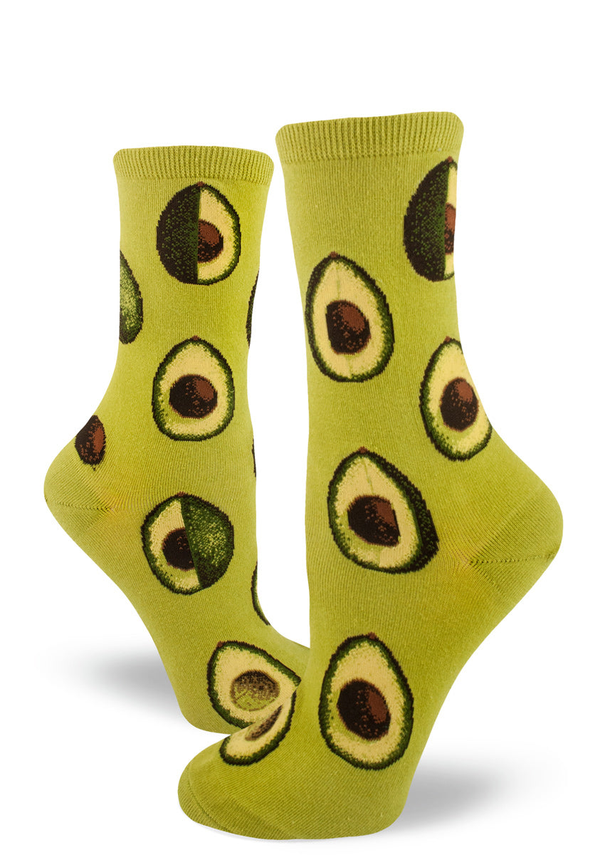 Cute avocado socks for women with avocados sliced open on a green background