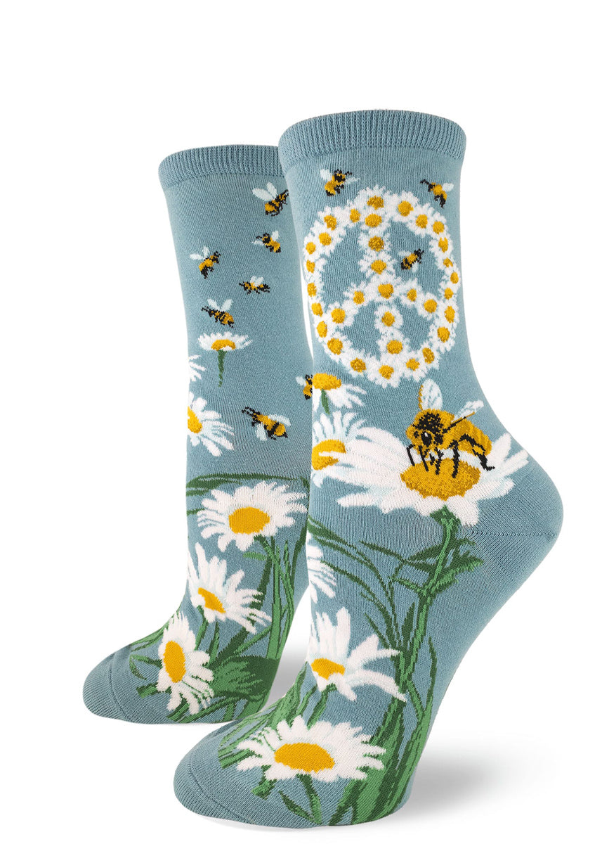 Bee socks for women with honeybees and daisy flowers forming a peace sign on a light blue background