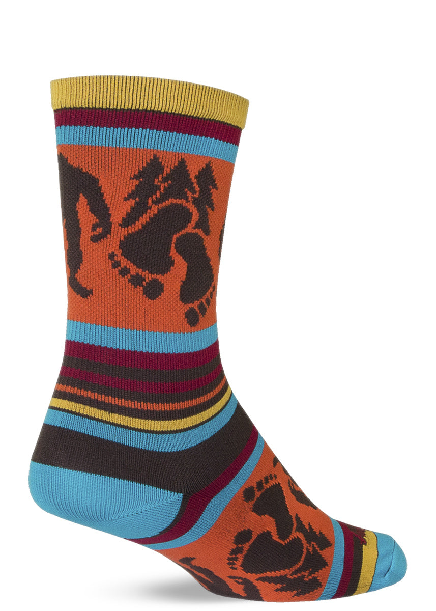 Fun Bigfoot socks with footprints, trees and Sasquatch on colorful striped athletic socks