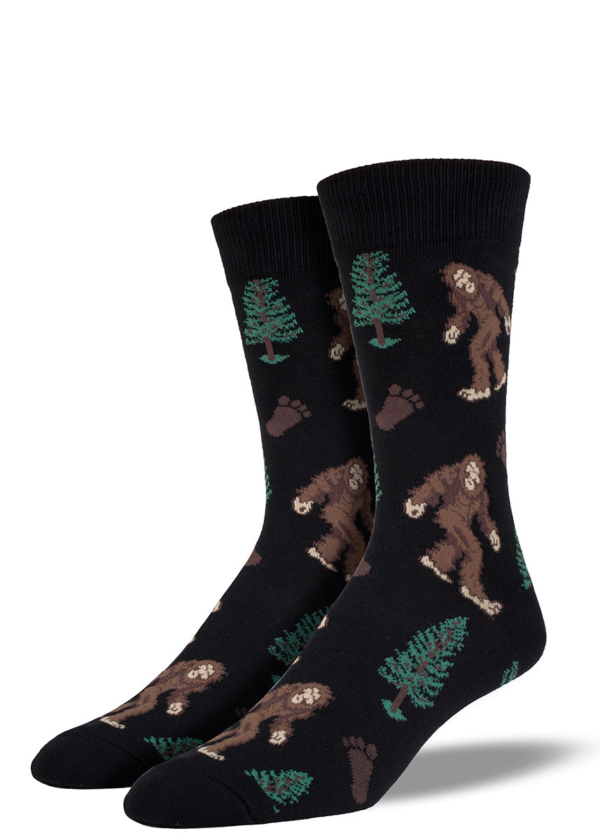 Bigfoot men's socks with Sasquatch and trees plus Bigfoot footprints on a black background