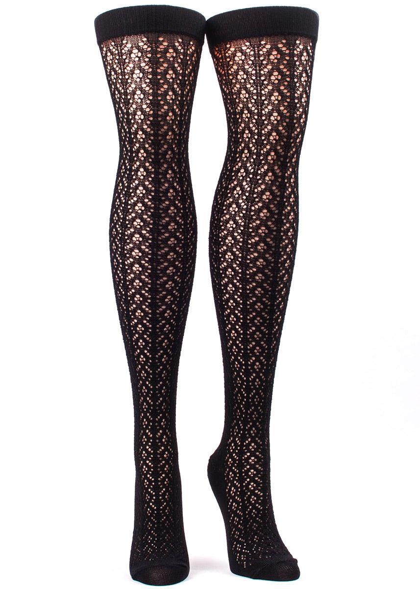 Over-the-knee socks for women feature a delicate crochet pattern in black.