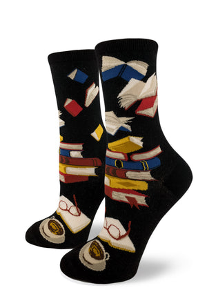 Book socks for women with stacks of books and flying books in the air on a black background
