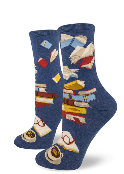 Women's book socks with piles of books, a book being read and flying books on a blue background