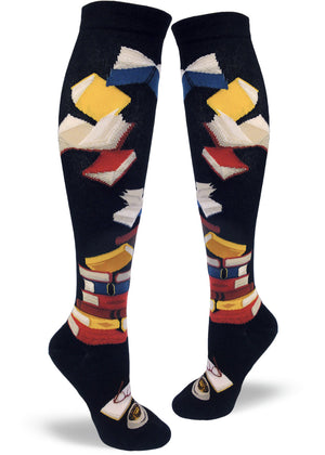 Knee-high book socks for women with stacks of books, flying books and a book being read on a black background