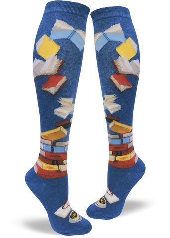 Book knee-high socks for women with books stacked and flying by on a blue background