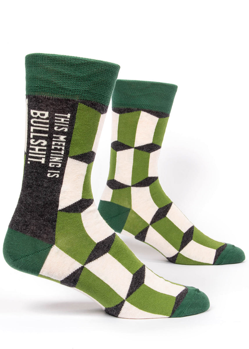 "Funny swear word men's socks that say ""This Meeting is Bullshit"" on a green patterned background."