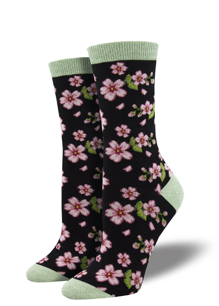 Bamboo crew socks for women feature sweet pink cherry blossom blooms on a black background.