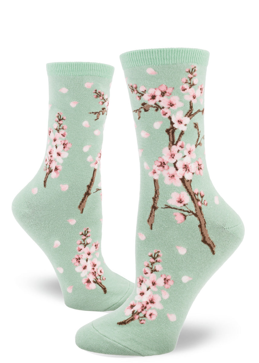 Spring socks for women feature pale pink cherry blossoms on a mint green background.