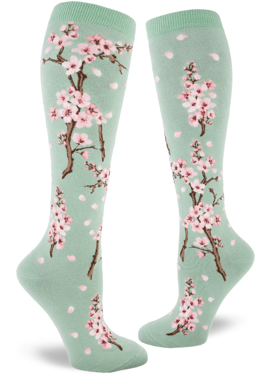 Knee socks for women feature pale pink cherry blossoms on a mint green background.