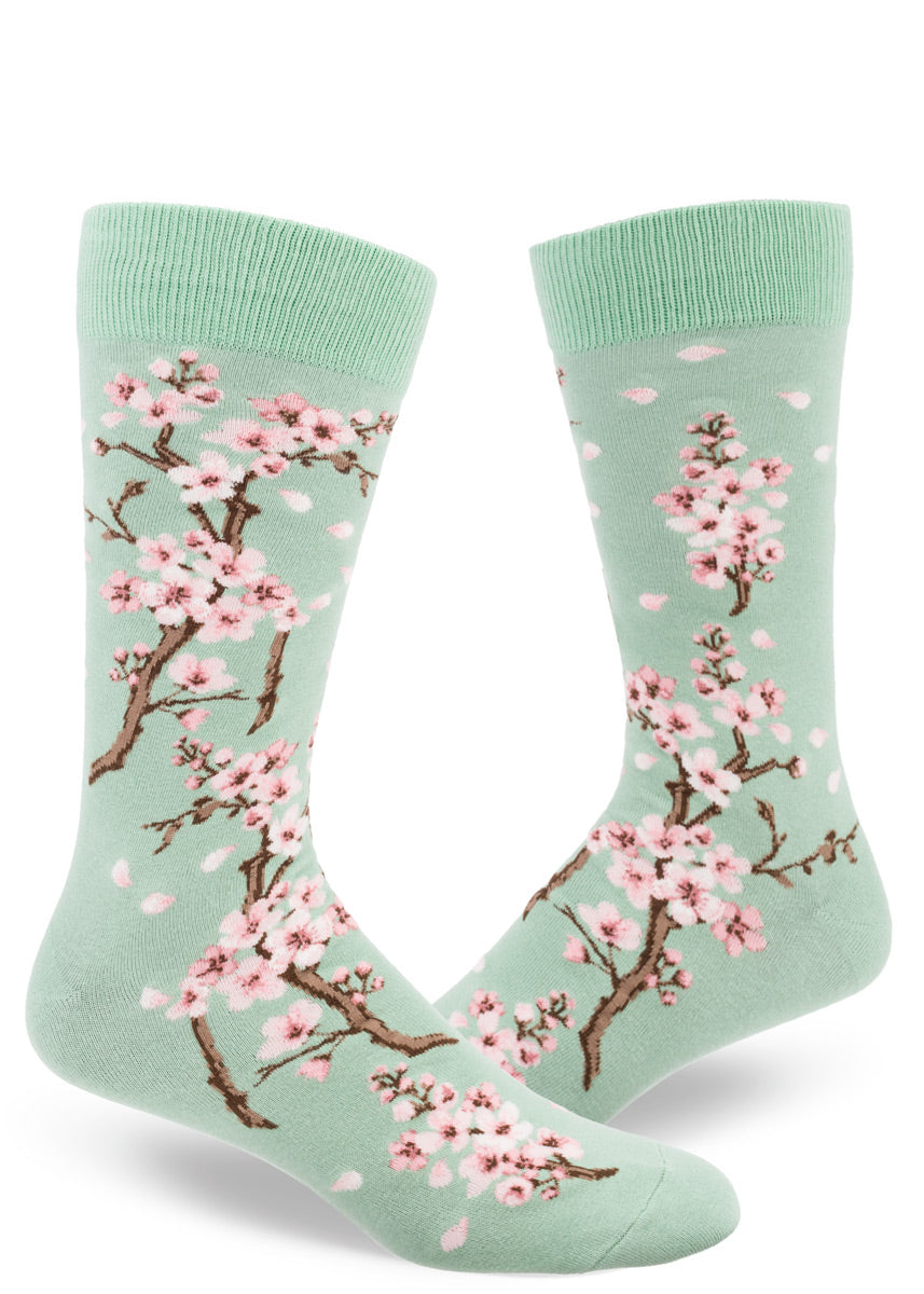 Spring crew socks for men feature pale pink cherry blossoms on a mint green background.
