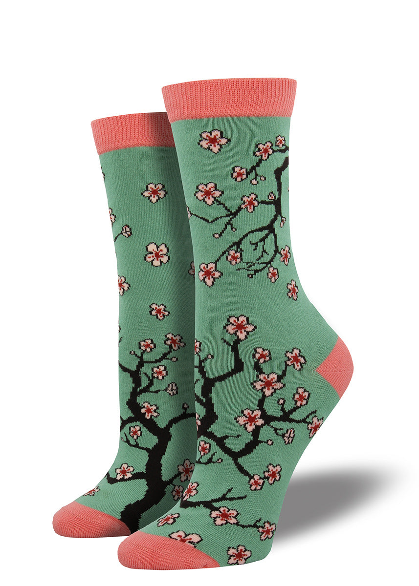 Cherry blossom bamboo socks for women with springtime flowers on a teal background