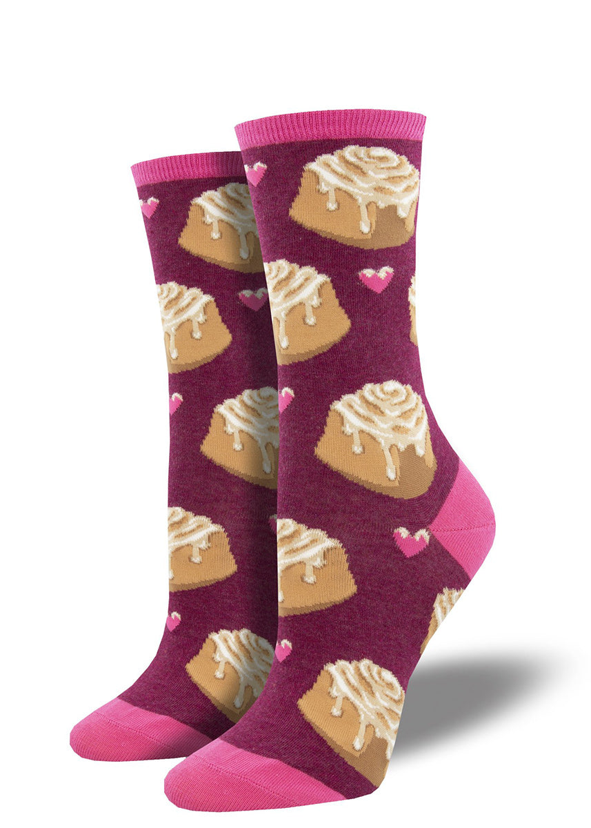 Cute socks for women feature delicious cinnamon rolls and little pink hearts on a dark pink background!