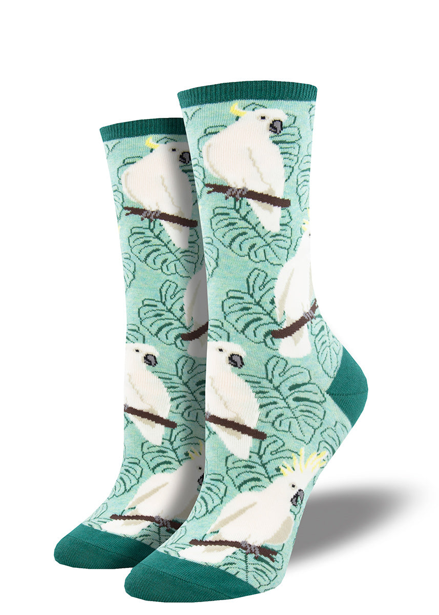 Crew socks for women feature cute white cockatoo birds with palm leaves in the background.