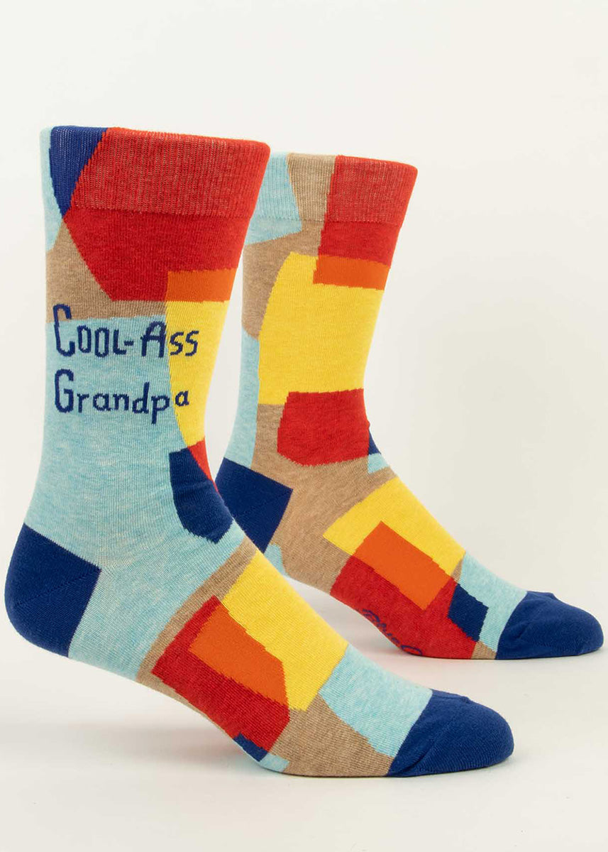 "Funny crew socks for men feature yellow, red, and blue shapes on a taupe background with the words, ""Cool-Ass Grandpa."""