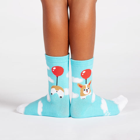 Cute corgi balloon socks for kids with dogs floating in the clouds beneath red balloons