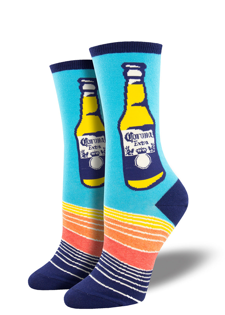 Crew socks for women feature full bottles of Corona beer on a blue background with sunset-colored stripes below.