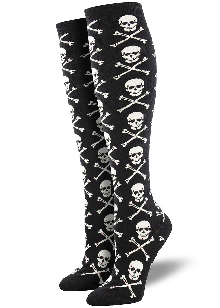 Knee-high socks for women feature a repeating pattern of a skull and crossbones on a black background.