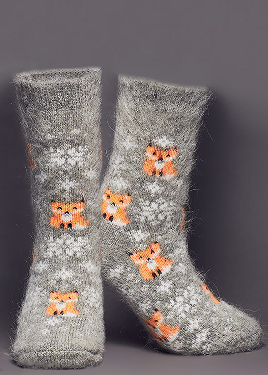Goat wool socks for women feature white snowflakes and adorable orange foxes on a gray background.