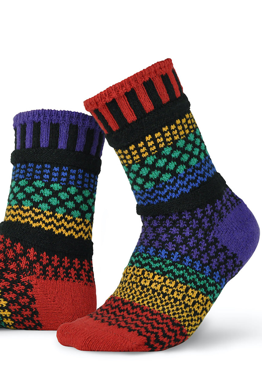 Mismatched socks feature funky patterns in bands of red, yellow, green, indigo, and purple.