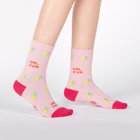 Sparkly girl power socks for kids with yellow lightning bolts on a pink background