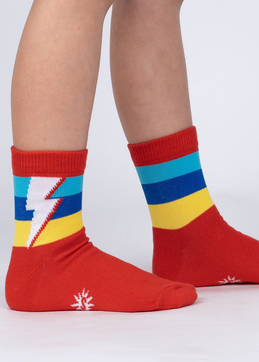 Crew socks for kids feature glow-in-the-dark lightning bolts on blue and yellow stripes on a red background!