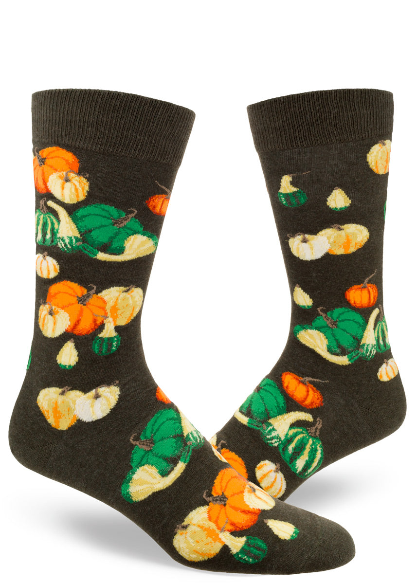 Autumn socks for men feature colorful pumpkins and other gourds on a mossy green background.