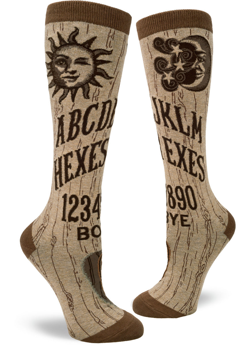 "Knee high socks for women are made to look like spirit boards with the alphabet, numbers, planchette, and the phrases ""Hexes for Exes"" and ""Boy Bye."""