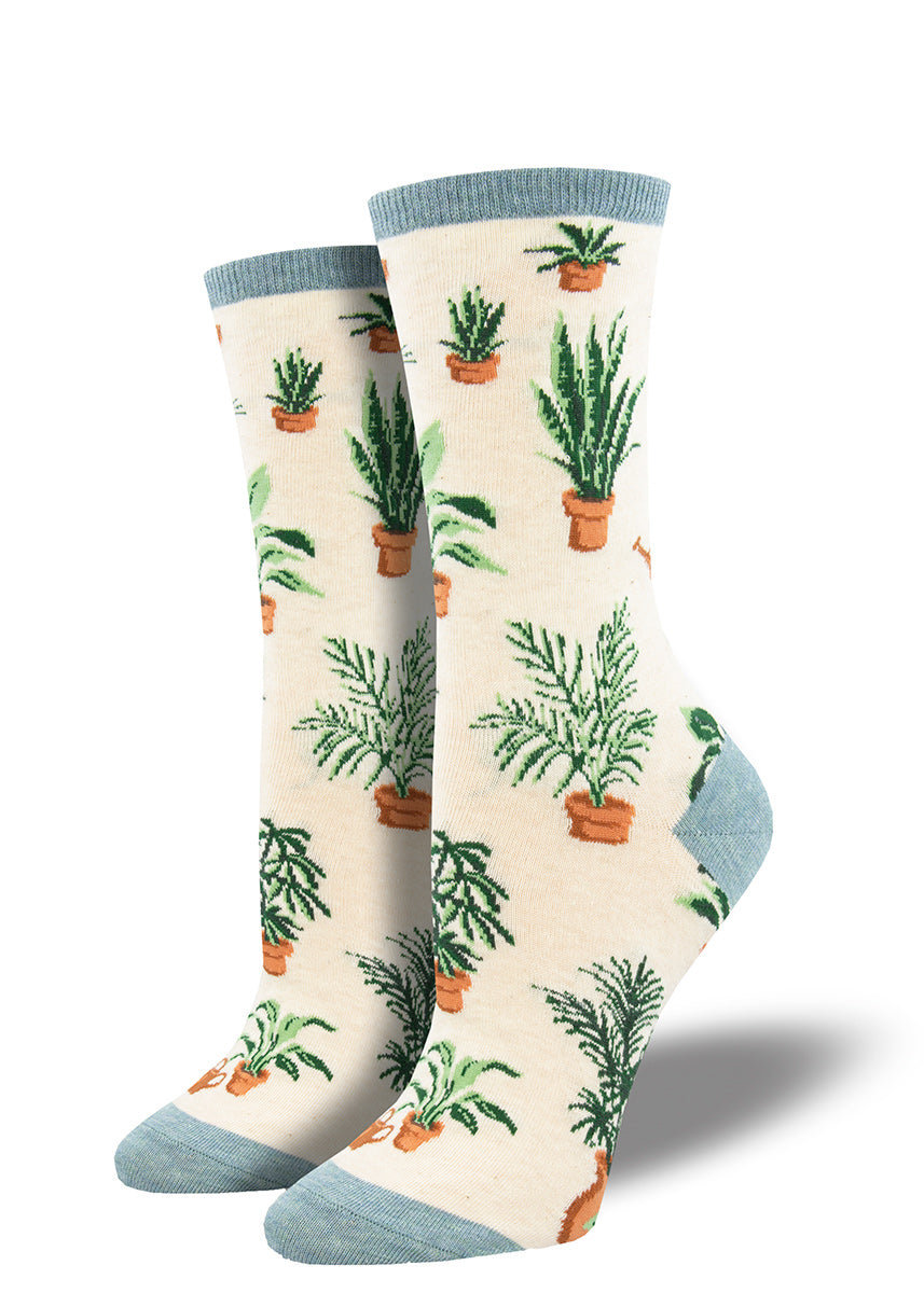 Crew socks for women are covered in a variety of potted plants on a heather cream background.