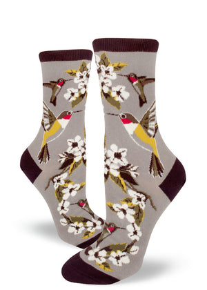 Hummingbird socks for women with ruby-throated hummingbirds drinking nectar from white flowers on a light gray background