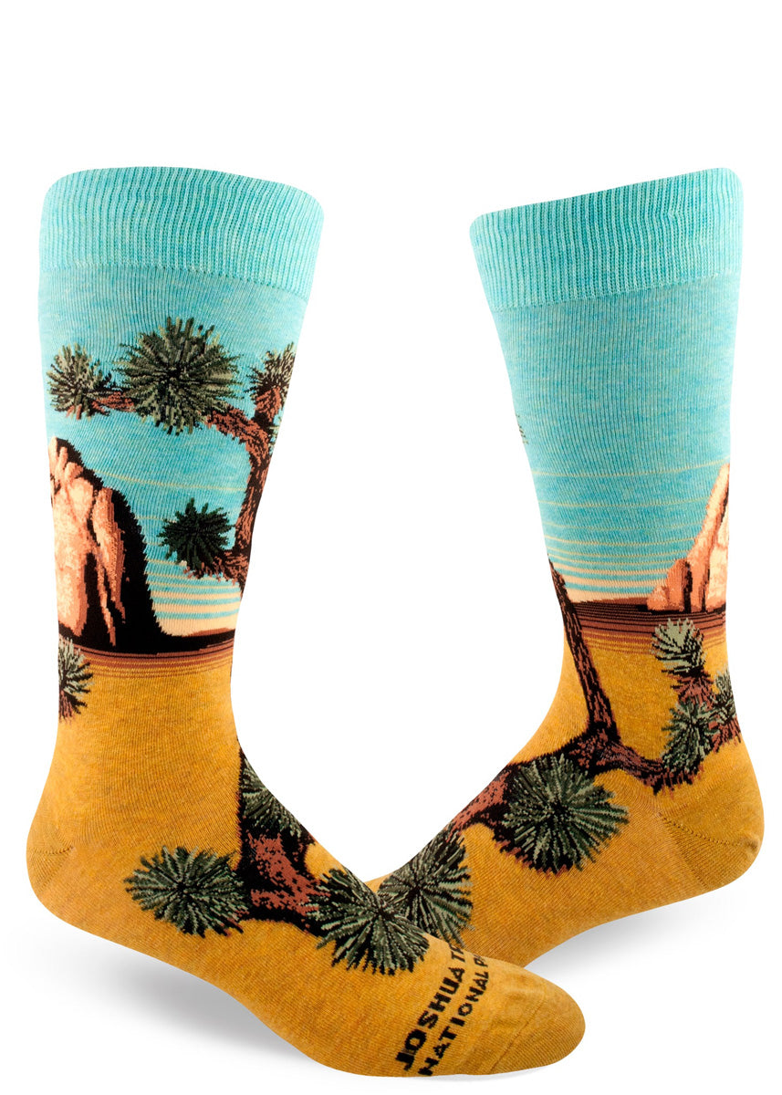 Crew socks for men depict Joshua Tree in all its glory, with golden desert sands, a rock formation, and aqua skies.