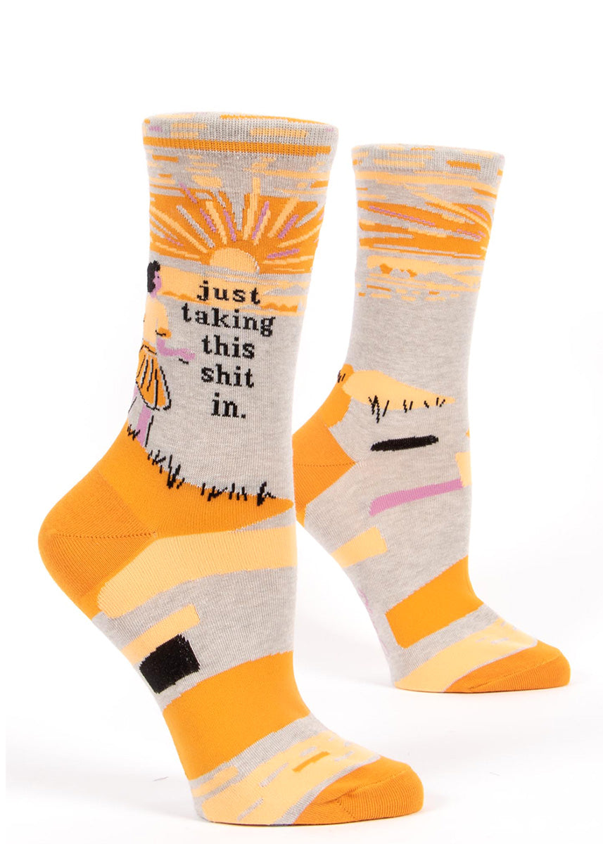 "Funny socks for women show a woman enjoying a sunset with the words, ""just taking this shit in."""
