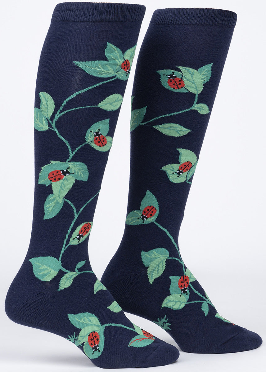 Ladybug knee socks for women feature adorable ladybugs crawling on green leaves.